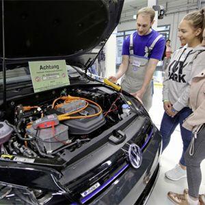 Kraftfahrzeug-Mechatroniker für System- und Hochvolttechnik zeigt Gästen an einem e-Golf, worauf bei Arbeiten an Elektro-Fahrzeugen zu achten ist.